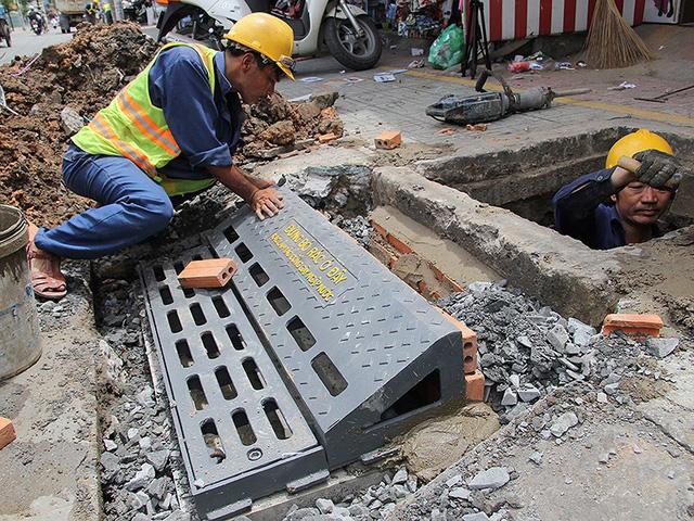 Công nhân lắp đặt thí điểm hố ga thông minh trên đường Lê Văn Thọ, quận Gò Vấp, TP.HCM. Ảnh: HOÀNG GIANG